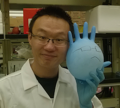 Portrait: Xwingwen Chen, holding a latex glove which has been blown up like a balloon. The glove has a face, created with marker.